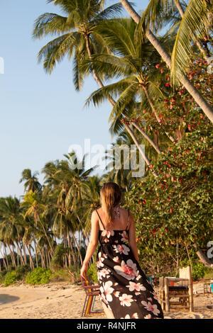 Rückansicht Blickrichtung von Frau mit langen sundress zu Fuß am Strand - Stockfoto