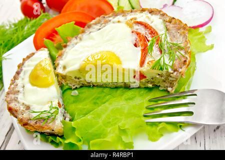 Törtchen mit Fleisch mit Ei und Tomate schnitt in die weiße Platte auf Salat, Brot und Dill auf dem Hintergrund Holzbretter - Stockfoto