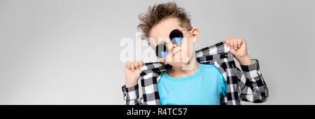 Ein schöner Junge in einem Plaid Shirt, blau Shirt und Jeans steht auf einem grauen Hintergrund. Der Junge trägt runden Brille. Rothaarige junge Holding seine Finger Collar Shirt - Stockfoto
