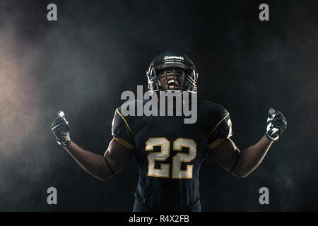 African American football player auf Schwarz isoliert. - Stockfoto