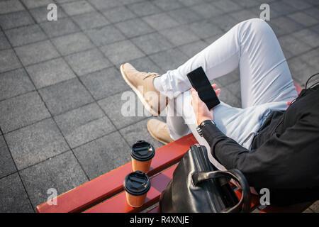 Schnittansicht der Mann in Jeans sitzt auf der Bank draußen und schwarz Telefon. Es re zwei Tassen und Ledertasche. - Stockfoto