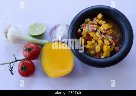 Mango Salsa in einem Stein Schüssel mit Zutaten in den Hintergrund - Stockfoto