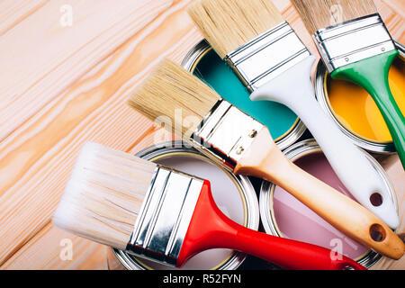 Vier offene Farbdosen mit Bürsten auf Holz- natürlichen Hintergrund. Gelb, Weiß, Rosa, Türkis Farben. Makro - Stockfoto