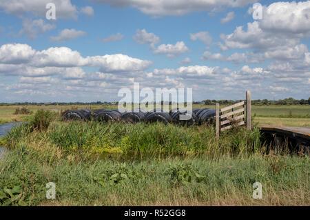 Heuballen in Kunststoff schwarz gewickelt und in eine Landschaft mit einem Creek und einen kleinen Zaun gestapelt, mit blauem Himmel und weißen Wolken. - Stockfoto