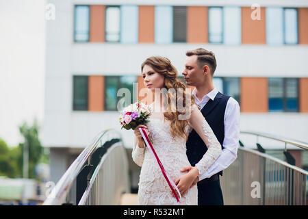 Braut und Bräutigam zu Fuß in die Stadt, Hochzeit, Ehe Konzept. Braut und Bräutigam im städtischen Hintergrund. junges Paar gehen auf eine Treppe in den Hochzeitstag. - Stockfoto
