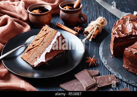 Teil der Schokoladentorte mit Marillenmarmelade Füllen mit Ganache auf eine schwarze Platte mit Glühwein in Ton rustikalen Cups auf einen bla serviert. - Stockfoto