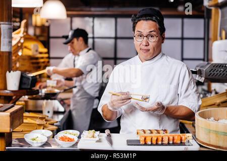 Schöner Mann holding Sushi mit Stäbchen