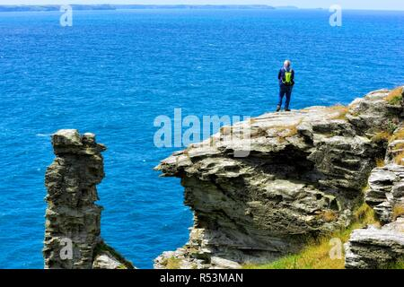 Ein Mann stand am Rand einer Klippe, Tintagel Halbinsel, Cornwall, England, Großbritannien - Stockfoto
