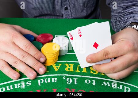 Casino Chips und Karten am grünen Tisch. Mann mit zwei Asse in der Hand. Spielsucht abstraktes Konzept. - Stockfoto