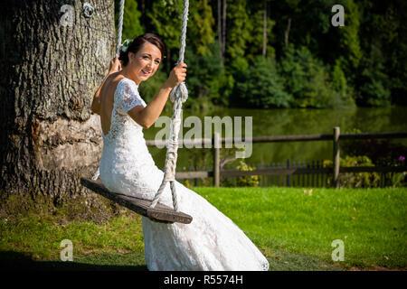 Sommer auf einer Schaukel Braut an ihrer Hochzeit sitzen in Cardiff South Wales - Stockfoto