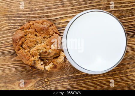 Knusprige zerbröckelt Weizen cookies auf einem Holztisch, close-up Essen und ein Glas weiße Milch zu einem besseren Geschmack zu dem Teig geben - Stockfoto