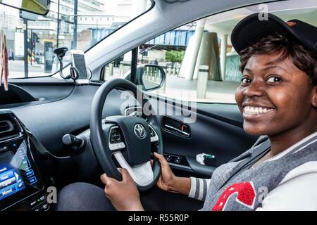 London England Vereinigtes Königreich Großbritannien Southwark uber Fahrer Auto Innenraum innen Lenkrad Schwarz lächelnde Frau arbeiten - Stockfoto