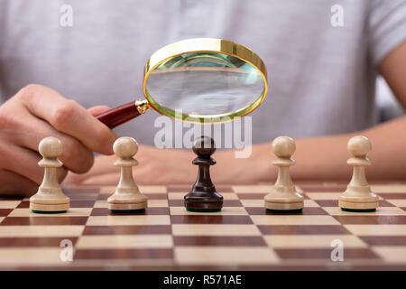 Close-up In eines Mannes Hand mit Lupe über schachfigur Schachfigur - Stockfoto