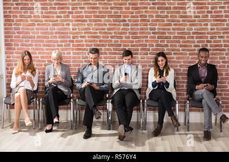 Die Menschen warten auf Job Interview mit Handy - Stockfoto