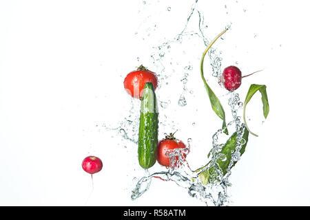 Die frischen Tomaten, Gurken, Rettich in Spray des Wassers. - Stockfoto