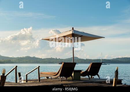 Tropical Beach Resort mit Liegestühlen und Sonnenschirmen in Phuket, Thailand. Sommer, Reisen, Ferien und Urlaub Konzept - Stockfoto