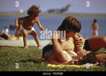 Verfassung Strand - in Bild und Ton von Logan Airport Start- und Landebahn 22R - Junge Mann und Frau Hug/Umarmung auf dem Boden liegend - Stockfoto