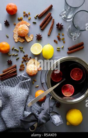 Glühwein in Aluminium Kasserolle auf grau Holztisch. Weihnachten und Winter wärmendes Getränk. Zutaten: Wein, Zitrone, Zimtstangen, Sternanis, Kardamom, - Stockfoto