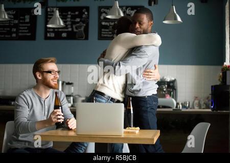 Happy multiethnischen Freunde Hug feiern Sieg in Kneipe hängen, aufgeregt, diverse Männer gratulieren mit Tor umarmen, Jungs haben Spaß - Stockfoto