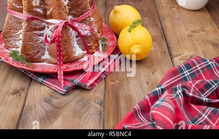 Traditionelle italienische Weihnachten Obstkuchen Panettone, Pandoro mit festlichen Red Ribbon und Weihnachtsschmuck. Auf einer hölzernen Hintergrund. Freier Speicherplatz für t - Stockfoto