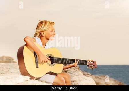 Seitenansicht Portrait von Teenager Gitarre spielen am Strand und schaut in die Ferne - Stockfoto