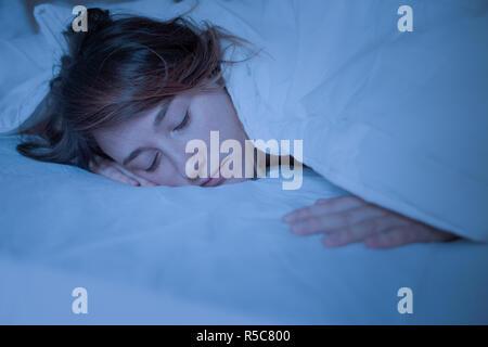 Gesicht Porträt von Frau schlafen nachts im Bett - Stockfoto