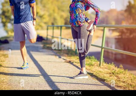 Junge Sport Frau und Mann sich bereit zu laufen und im freien Ausübung