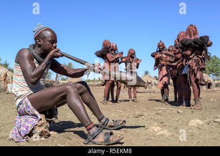 Gruppe von Frauen Himba mit traditionellen Kleider tanzen im Kreis, während ein Mann spielt eine Trompete aus einem orix Horn. - Stockfoto