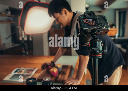 Fokus auf Kamera Filmen männlichen Fotograf styling Essen mit Magazin auf Tisch. Fotograf Aufnahme Inhalt auf Kamera im Studio auf Food-fotografie. - Stockfoto
