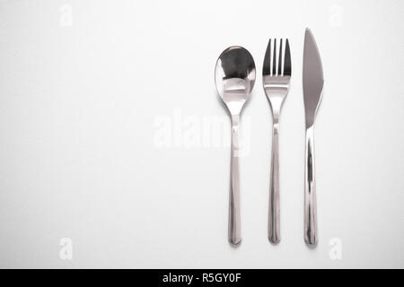Glänzendes Metall besteck Gabel Messer Löffel zum Essen Mahlzeit im Restaurant grauer Hintergrund - Stockfoto