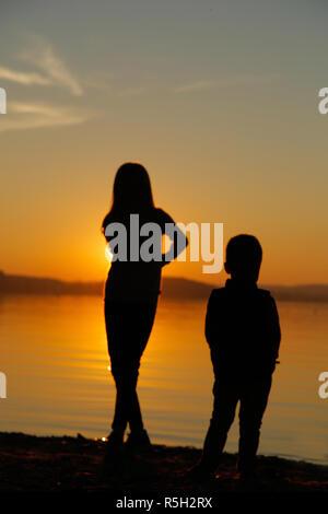 Mädchen mit einem Jungen auf den Strand schauen in die Ferne - Stockfoto