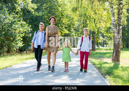 Glückliche junge Familie, Mutter mit drei Kindern gehen in den Park. Gesunder Lebensstil Konzept - Stockfoto