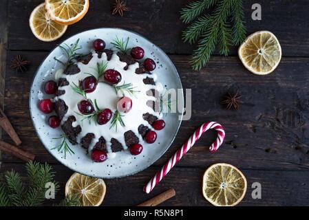 Christmas Pudding, Obst Kuchen mit Puderzucker und Preiselbeeren auf rustikalen Holztisch eingerichtet, Ansicht von oben. Hausgemachte, traditionelle Weihnachten Dessert - Christm - Stockfoto