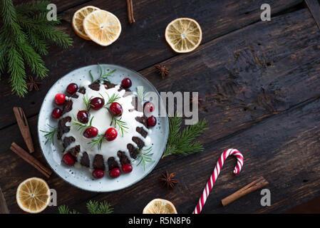 Christmas Pudding, Obst Kuchen mit Puderzucker und Preiselbeeren auf rustikalen Holztisch eingerichtet, Kopieren, Ansicht von oben. Hausgemachte, traditionelle Weihnachten desser - Stockfoto