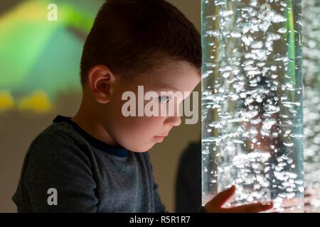 Kind in der Therapie sensorische Stimulation, snoezelen. Kind Interaktion mit farbigen Lichtern bubble Rohr Lampe während der therapiesitzung. - Stockfoto