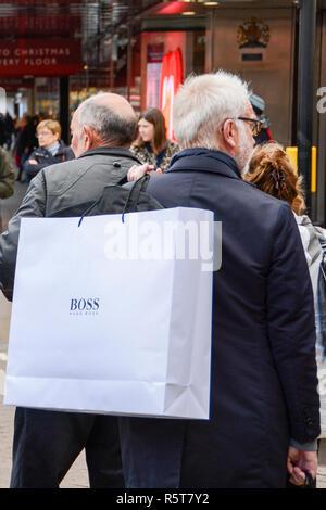 Zwei männliche Käufer an einer geschäftigen Oxford Street, die Hugo Boss Papier tragetaschen auf ihren Schultern - Stockfoto