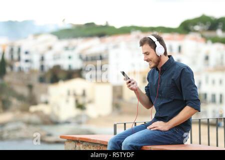 Glückliche Menschen mit Kopfhörern hören die Musik auf einem Felsvorsprung mit einer Stadt im Hintergrund - Stockfoto