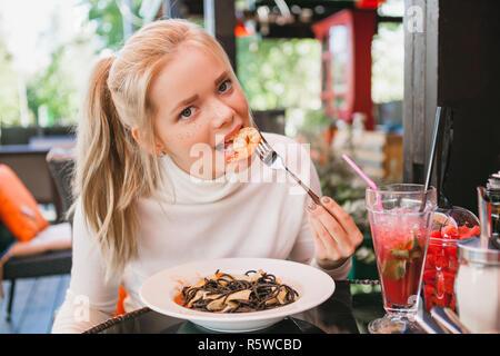 Junge schöne Frau essen schwarze Nudeln mit Meeresfrüchten und Tintenfisch Tinte in das Restaurant im Freien. Lustig und schön.