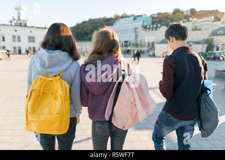 Ansicht von der Rückseite auf drei High School Schüler. Stadt Hintergrund, goldene Stunde. - Stockfoto