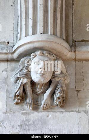 Crouching Abbildung mit Geschnitztem Gesicht dekoriert auf Corbel in St. Johannes der Täufer Pfarrkirche, Bishopstone, Wiltshire. - Stockfoto