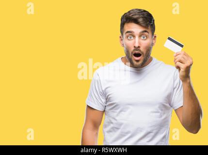 Jungen gutaussehenden Mann mit Kreditkarte über isolierte Hintergrund im Schlag mit einer Überraschung konfrontiert, ängstlich und aufgeregt mit Angst Angst Ausdruck - Stockfoto
