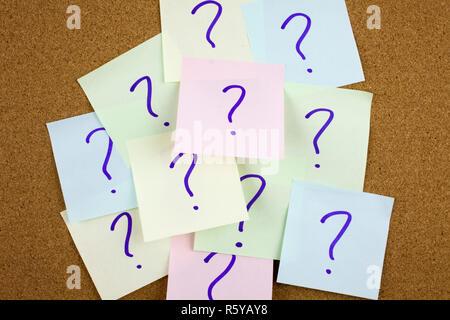 Eine gelbe Haftnotiz schreiben, caption, Beschriftung Haufen von bunten Papier nimmt mit Fragezeichen. Nahaufnahme. - Stockfoto