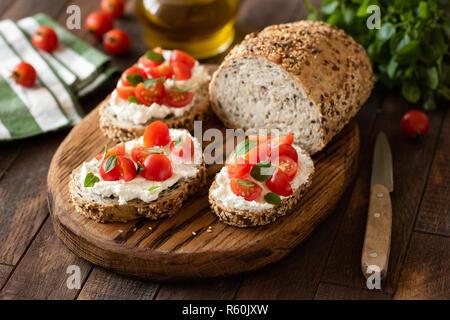 Bruschetta mit ricotta Käse und Kirschtomaten auf Vollkornbrot mit Samen. Auf hölzernen Schneidebrett serviert. - Stockfoto