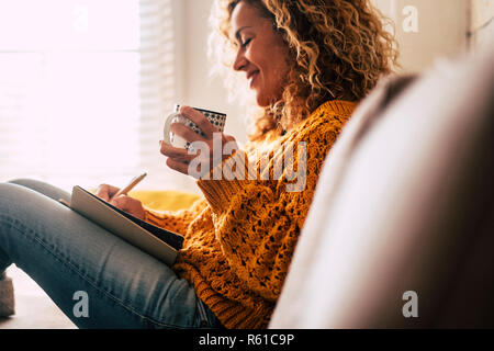 Gerne nette Dame zu Hause Notizen auf ein Tagebuch schreiben, während Sie eine Tasse Tee und Rest trinken und entspannen Sie eine Pause. Herbst Farben und Personen, die zu Hause leben