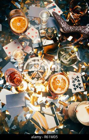 Ansicht von alkoholischen Cocktails, Karten spielen, Zigaretten, gerollte Banknoten, Kreditkarten und Kokain auf Tabelle von golden Konfetti bedeckt - Stockfoto