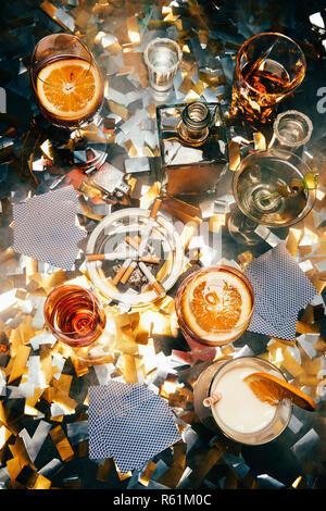 Flach mit Zigaretten, alkoholische Cocktails, Whiskey und Karten spielen am Tisch von golden Konfetti bedeckt - Stockfoto