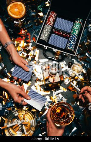 Teilweise mit Blick auf die Frauen poker Spielen am Tisch mit Whiskey, alkoholfreien Cocktail und Zigaretten und golden Konfetti - Stockfoto
