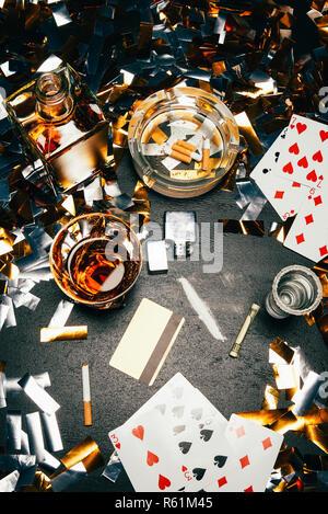 Blick von oben der Karten, Zigaretten, Whiskey, gewalzt, Banknote, Kreditkarte und Kokain auf Tabelle von golden Konfetti bedeckt - Stockfoto