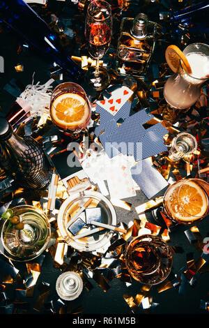 Flach mit Zigaretten, alkoholische Cocktails, Whiskey und Partei Hörner auf Tabelle von golden Konfetti bedeckt - Stockfoto