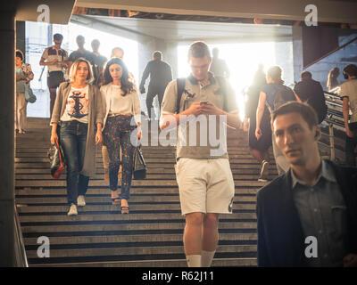 Moskau, Russland - September 6, 2018: Gewöhnliche Leute gehen, und gehen Sie auf die U-Bahn zur Hauptverkehrszeit. Menschen hinunter in die Unterführung. Silhouetten von Menschen zu Fuß auf der Treppe vor dem Hintergrund der Sonne. - Stockfoto